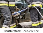 Small photo of Firefighters working on an auto vehicle extrication with a hydraulic power rescue tool