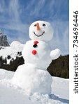 funny snowman against swiss alps | Shutterstock . vector #734696446