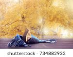 small house in warm scarf on... | Shutterstock . vector #734882932