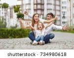 young family posing with a key... | Shutterstock . vector #734980618