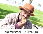 An Elderly Homeless Man Eats A...