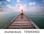 woman practicing yoga at... | Shutterstock . vector #735043402