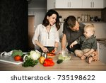 family in the kitchen cooking | Shutterstock . vector #735198622
