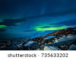Northern lights over the fjord and mountains, nearby Nuuk city, Greenland