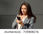 Small photo of Shocked middle aged woman reading a text message on her mobile phone with an aghast expression