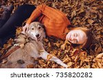 Stock photo long haired red haired girl in a fashionable sweater plays with her big gray dog 735820282
