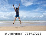 happy man jumping at the beach... | Shutterstock . vector #735917218