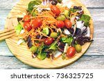 fresh salad on a wooden plate   Shutterstock . vector #736325725