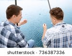 Two Men Fishing From Pier On...