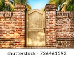 Wooden Gate In A Brick Fence