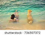 Stock photo woman relax with golden retriever dog at the beach 736507372