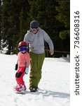 Small photo of At Sunny Cold Winder Day at Mountain Ski Resort Mount Hood Meadows Oregon Father Teaching Little Daughter Snowboarding , Vertical picture