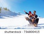 young couple sledding and...