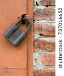 old padlock on metal door. red... | Shutterstock . vector #737016652