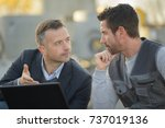 suited man and workman looking... | Shutterstock . vector #737019136