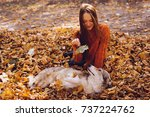 Stock photo young red haired girl walking with her big dog in the park playing with it in a pile of autumn 737224762