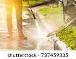 worker cleaning driveway with... | Shutterstock . vector #737459335