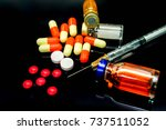 Small photo of Plastic syringe, capsule medicines, injection drug in vials, white and red pills medicines isolate on black background. Suppose to amphetamine or narcotic addiction.