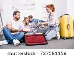 happy family packing luggage... | Shutterstock . vector #737581156