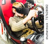 Small photo of AUTOSHOW PRAHA, CZ - OCT 7, 2017: Virtual reality glasses in car video game. Boy with black Oculus VR RIFT or GO headset sits in moving sportscar seat, holds steering wheel, drives in unreal 3d space.