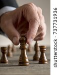 Small photo of Man playing chess moving black queen piece in a close up view. Conceptual of business strategy planning.