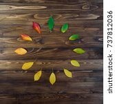 Small photo of Natural watch from autumn leaves. Clock concept. Autumn leaves transition from green to red on wooden background. Concept change of season.