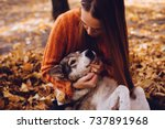 Stock photo a young red haired girl is walking with her big gray dog in the park in a pile of autumnal fallen 737891968