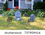 Small photo of Halloween outdoor decoration background.Front yard of private house decorated by fake skull,bones hands,tombstones and grates,pumpkins on the porch for old american trick-or-treat Halloween tradition.