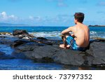 Man sitting on the lava rocks near the ocean and looking at the Island from West Maui. Hawaii. - stock photo