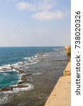Small photo of Embankment with sea wall against Mediterranean Sea background. Old city of Acre, Israel.