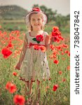 Small photo of Cute blond young girl child stylish dressed in white handmade hooked dress wearing airy hat top posing on meadow of forest poppy poppies Adoreable scene.