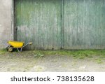 yellow wheelbarrow and part of green vertical planks of old barn doors with peeling paint and grassy brick pavement - stock photo