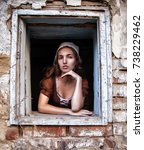 Small photo of sad woman in a rustic dress sitting near window in old house feel lonely. Cinderella style