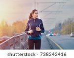 Small photo of Young woman jogging on the street early in morning. Fit and healthy brunette girl working out during winter in the city. Runner work out in an urban context on bridge.
