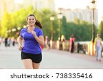 overweight young woman jogging... | Shutterstock . vector #738335416