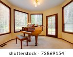Piano room with yellow walls and many windows - stock photo