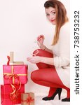 Small photo of Woman in high heels shoes red pantyhose with many presents putting the bracelet in gift box. Christmas season celebration concept.