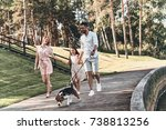 Stock photo family day full length of young family of three holding hands and smiling while walking in the park 738813256