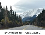 Lone car on a Canadian highway through the snow capped Rocky Mountains