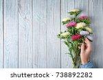 woman arranging bouquet of... | Shutterstock . vector #738892282