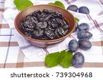 Small photo of Still life with plums and prunes in a ceramic bowl on the table. Prune and harvest of fresh plums. Plums, prunes and green leaves.