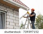 worker installs the gutter... | Shutterstock . vector #739397152
