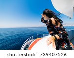 Small photo of Woman looking like a capitan to a far on yacht