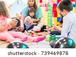 Stock photo dedicated young female kindergarten teacher holding a pre school shy girl while watching children 739469878