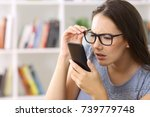 Small photo of Girl wearing eyeglasses with eyesight problems trying to read phone text at home