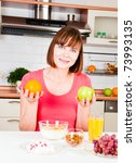 beautiful woman holding a green apple and orange - stock photo