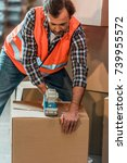 Small photo of male warehouse worker packing box with adhesive tape