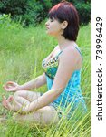 Young girl in lotus pose in the park - stock photo