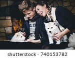 Stock photo loving beautiful couple man and woman holding white hussy puppies playing with them laughing 740153782