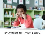 african boy sitting at his desk ... | Shutterstock . vector #740411092